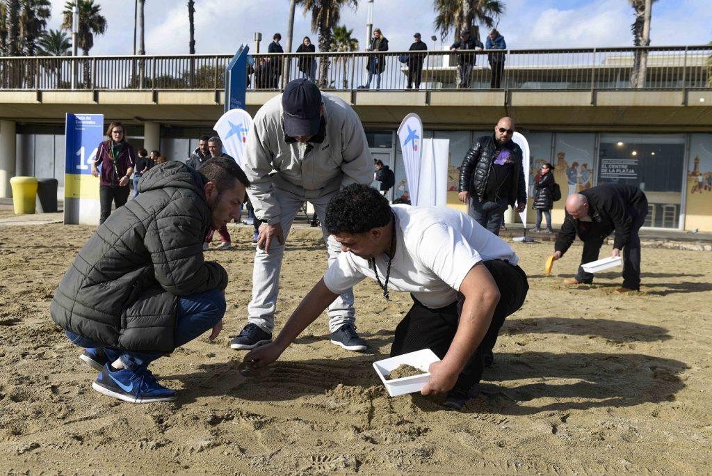 40 personas en riesgo de exclusión social participan en la limpieza de la playa del Somorrostro